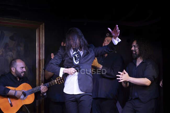 Hombre en traje negro bailando flamenco cerca de músicos masculinos hispanos durante la actuación contra la pintura en el escenario oscuro - foto de stock