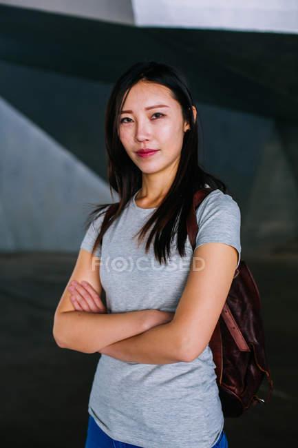 Mulher asiática confiante em roupa casual mantendo os braços cruzados de pé contra um fundo geométrico — Fotografia de Stock