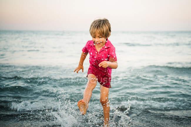 Menino feliz salpicando em águas rasas se divertindo na costa no crepúsculo — Fotografia de Stock