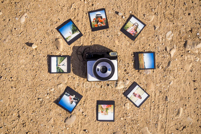 Stylish accessories and instant photos on sandy ground — Stock Photo