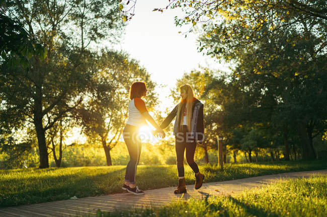 Cheerful young women looking at each other while spending time in green park against bright sun together — Stock Photo