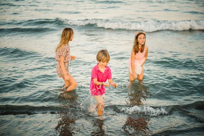 Gruppo di ragazzini con due sorelle che giocano in acque poco profonde sulla costa — Foto stock