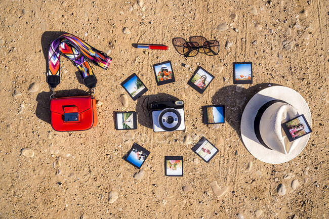 Various trendy accessories and bunch of instant pictures placed around photo camera on sandy ground on sunny summer day — Stock Photo