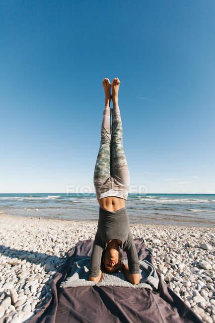 Афроамериканская молодая женщина в стойке на голове на фоне спокойного моря в солнечный день — стоковое фото