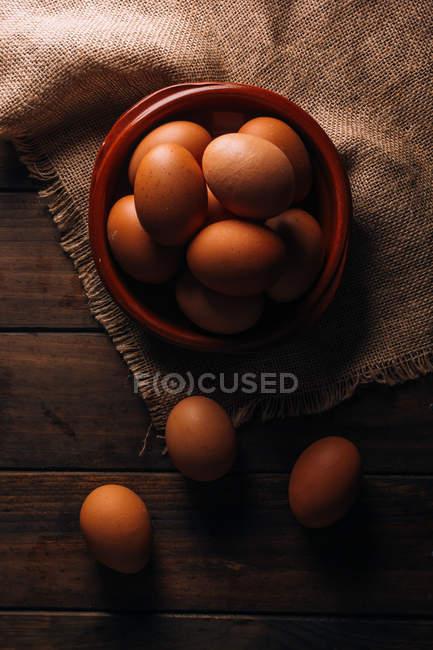 Hühnereier mit Schale und Sacktuch auf Holztisch — Stockfoto