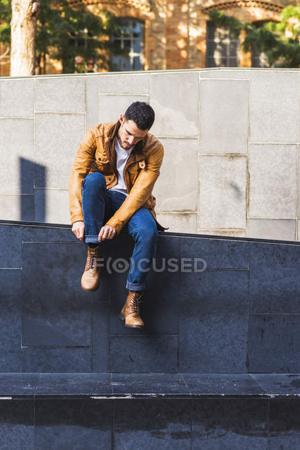 Confident trendy young guy sitting in concrete step outside contemporary building on city street — Foto stock
