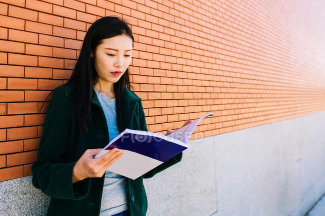 Asiatico donna lettura libro di testo mentre appoggiato sul muro di mattoni nel campus universitario — Foto stock