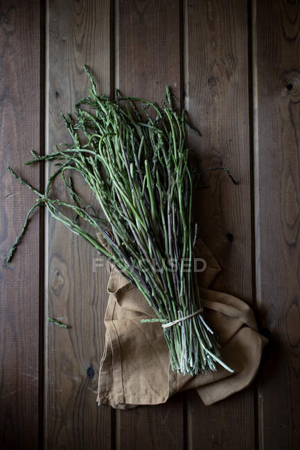 From above of bundle of green asparagus on wooden table — Stock Photo