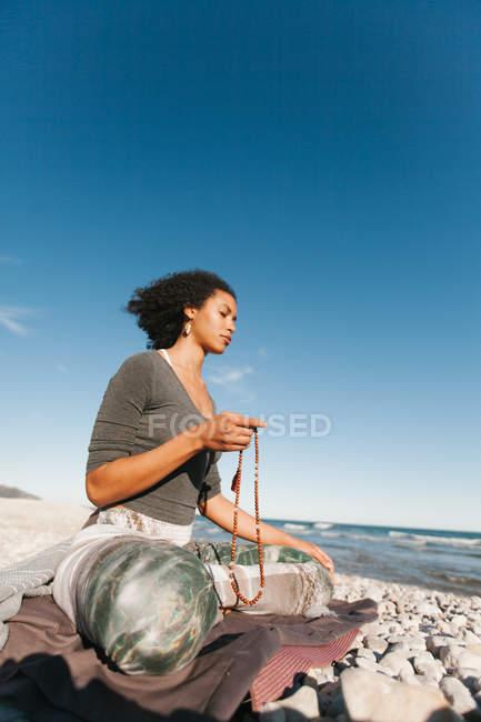 Приваблива молода жінка медитує і молиться носіння japamala комір в позі Lotus йоги на піщаному пляжі в світлий день — стокове фото