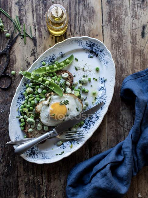 Сервированная тарелка с зеленым горошком и жареным яйцом на деревянном столе — стоковое фото