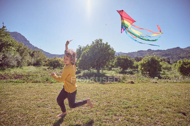Happy kid playing with colorful kite flying in blue sky on nature background — Stock Photo