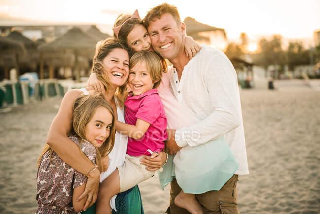 Дорослі чоловіки і жінки з сином і дочками стоять разом на пляжі, освітлені посмішкою в камері — стокове фото