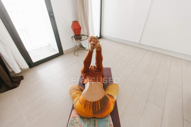 Anonymous woman performing yoga pose and stretching hands on mat in light room — Stock Photo
