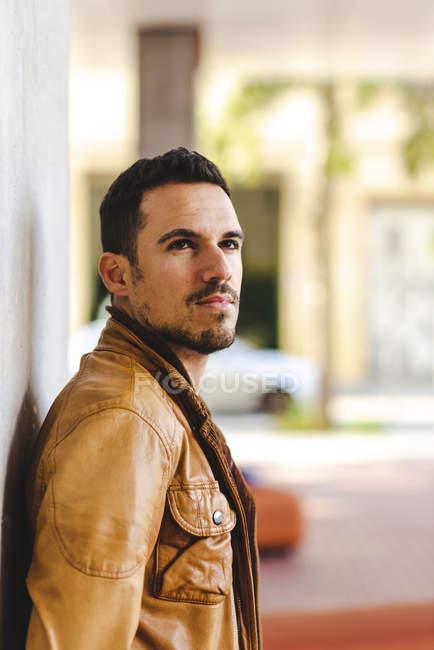 Вдумчивый модный молодой парень, опирающийся на бетонную стену на улице на размытом фоне — стоковое фото