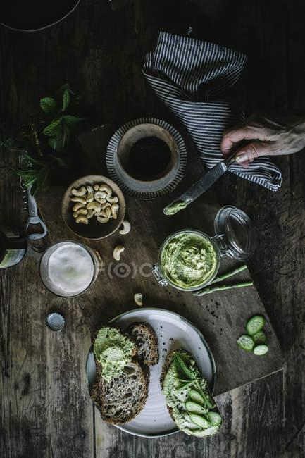 De arriba mano de persona irreconocible haciendo tostadas con paté de anacardo verde y rodajas de pepino sobre tabla de madera - foto de stock