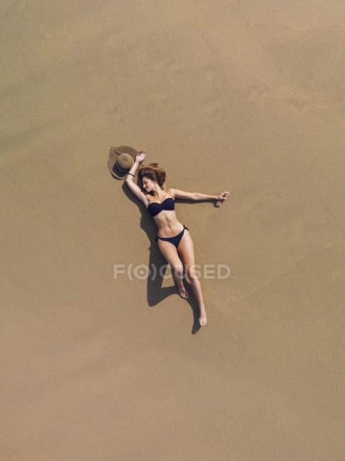 Mulher nova relaxed no Swimwear preto que relaxa na costa arenosa no dia ensolarado — Fotografia de Stock