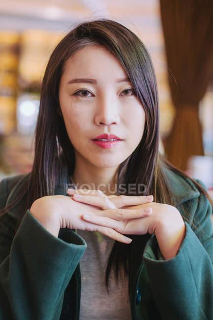Азійка в стильному зеленому пальто дивиться на камеру, сидячи за кафе. — стокове фото