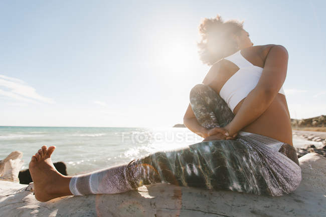 African American woman doing titibasana yoga posture on sunny beach — Stock Photo