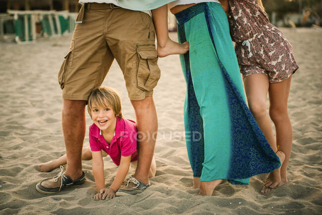 Adorable happy boy on sandy beach with crop parents and siblings spending time together — Stock Photo