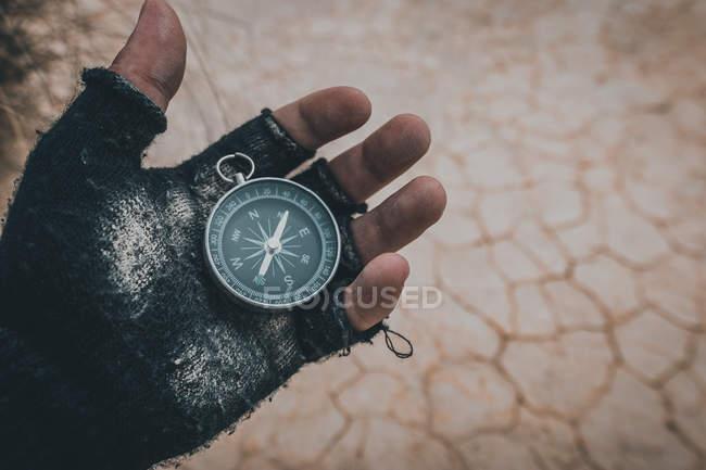 Primo piano della mano in guanto nero senza dita che tiene bussola sul luogo deserto — Foto stock