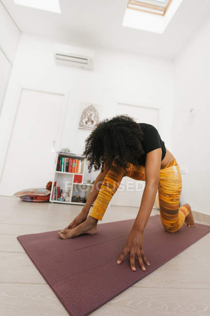 African American woman performing yoga pose with head down and stretching on mat in light room — Stock Photo