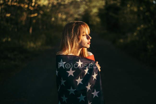 Молодая женщина с флагом США в сельской местности — стоковое фото