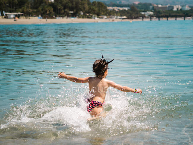 Vista posteriore di anonimo gioioso ragazza carina giocare in acqua di mare su sfondo di spiaggia calma — Foto stock