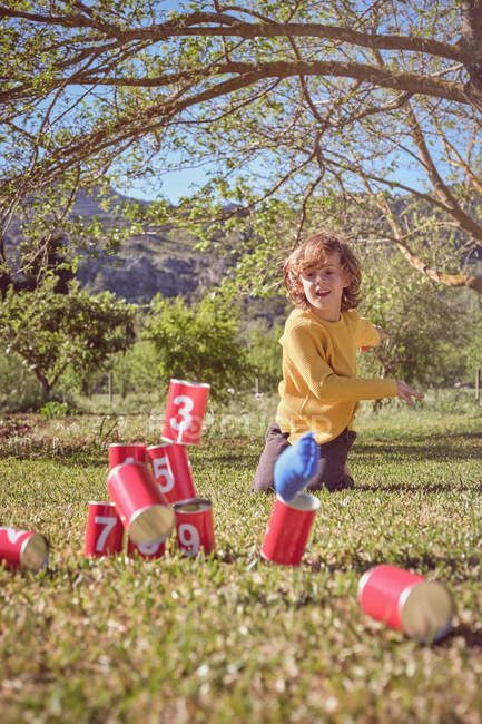 Cheerful kid kneeling and throwing ball in pyramid of red tin cans on nature background — Stock Photo