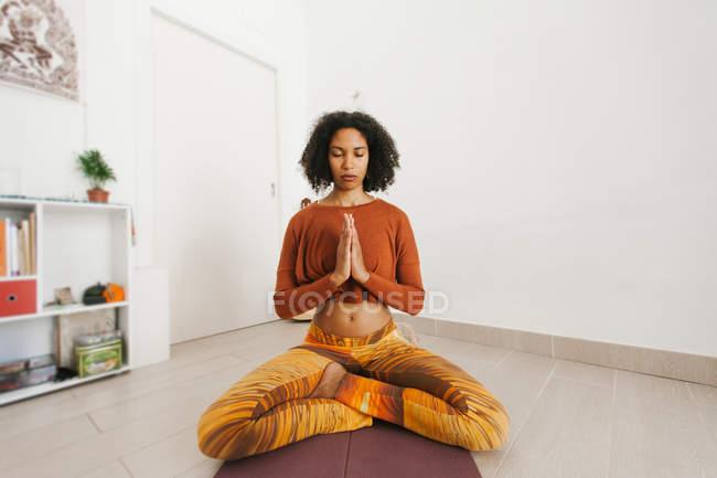 Афроамериканская молодая женщина, занимающаяся йогой, со скрещенными ногами и медитирующая с закрытыми глазами дома — стоковое фото