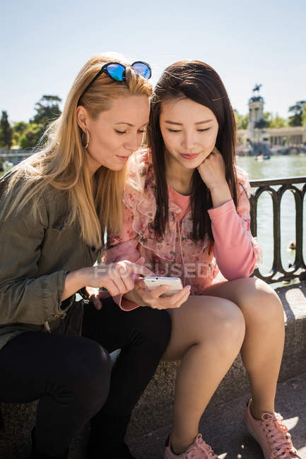 Young multiracial women in trendy outfits smiling and browsing smartphone while sitting near embankment railing — Stock Photo