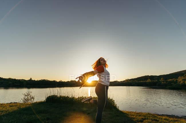 Mulher de pé no lago ao pôr do sol — Fotografia de Stock