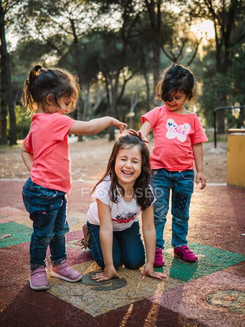 Fröhliche Kleinkind-Zwillinge spielen an Sommertagen mit lachender Freundin auf Spielplatz — Stockfoto