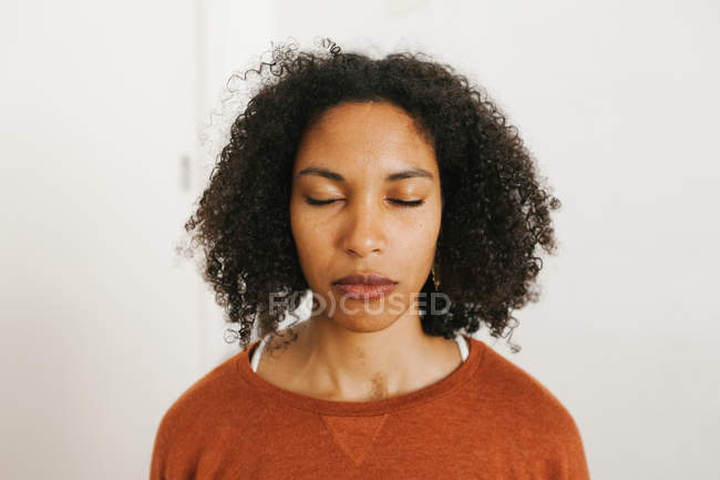 Closeup of young woman meditating with closed eyes against white background — стокове фото