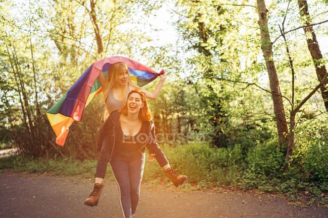 Mujeres alegres con bandera LGBT en la naturaleza - foto de stock