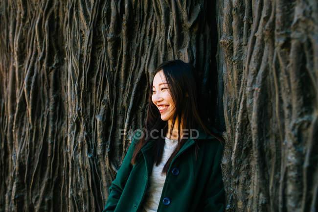 Взволнованная азиатская женщина в трикотажном наряде улыбается и отводит взгляд, опираясь на стену с рельефными корнями деревьев — стоковое фото