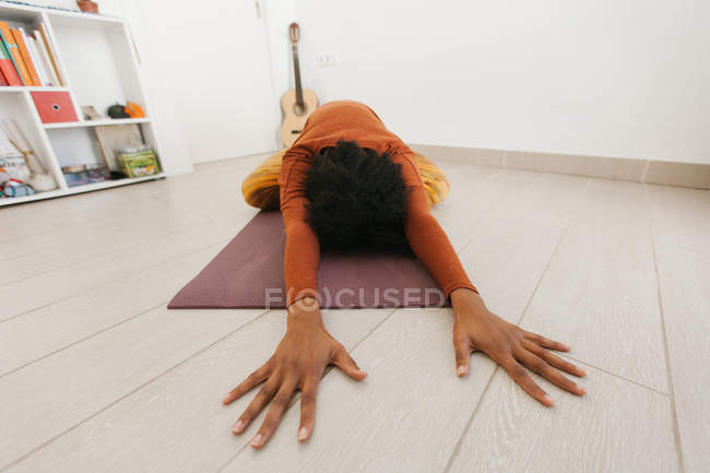 Anonymous woman performing yoga pose and stretching on mat in light room — Stock Photo