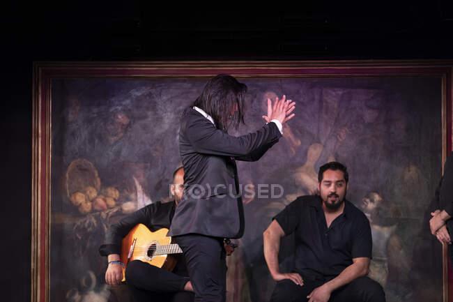 Человек в черном костюме танцует фламенко возле латиноамериканских музыкантов во время выступления против живописи на темной сцене — стоковое фото