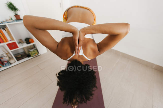 Anonymous woman performing yoga posture with folded hands behind back in light room — Stock Photo