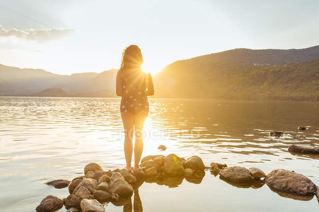 Back view of a unrecognizable woman standing on rock in water looking at mountains in sunset light — Stock Photo