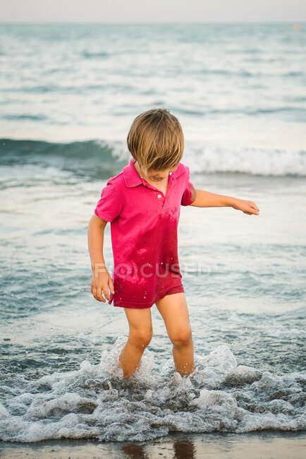 Happy little boy splashing in shallow water having fun on seashore in twilight time — Stock Photo