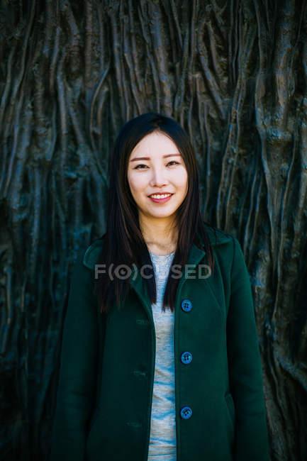 Mulher asiática excitada na roupa da moda sorrindo e olhando para longe enquanto se inclina na parede com alívio das raízes das árvores — Fotografia de Stock