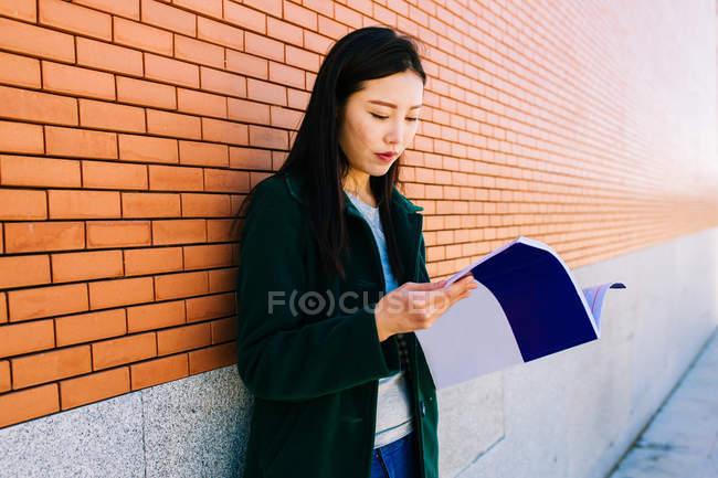 Азійка читає підручник, спираючись на цегляну стіну в університетському містечку. — стокове фото