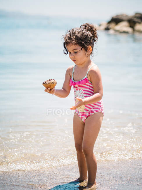 Adorable toddler girl in swimming suit standing in warm water of calm sea playing with a seashell — Stock Photo