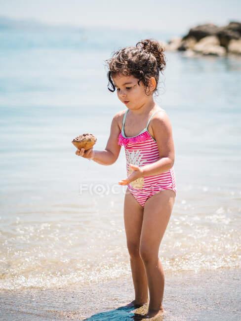 Adorabile bambina in costume da bagno in piedi in acqua calda del mare calmo che gioca con una conchiglia — Foto stock