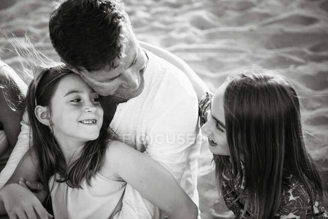 Uomo con le figlie sedute insieme sulla spiaggia nella parte posteriore illuminata sorridente a vicenda, foto in bianco e nero — Foto stock