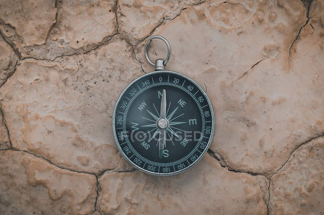 Round compass pointing to north on desert cracked ground — Stock Photo