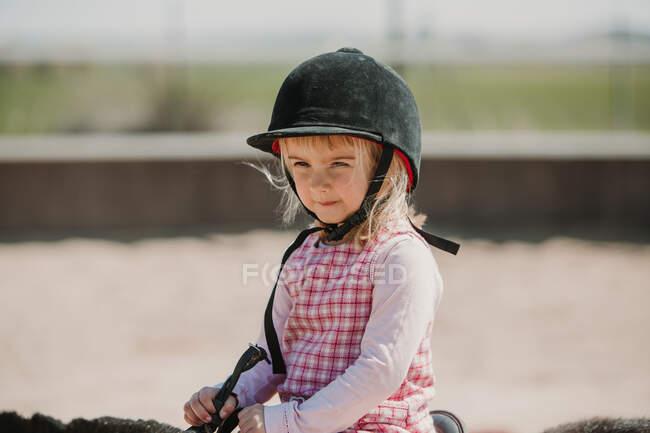 Niña en vestido y heno de jinete sentado a caballo mientras aprende a montar en el hipódromo - foto de stock