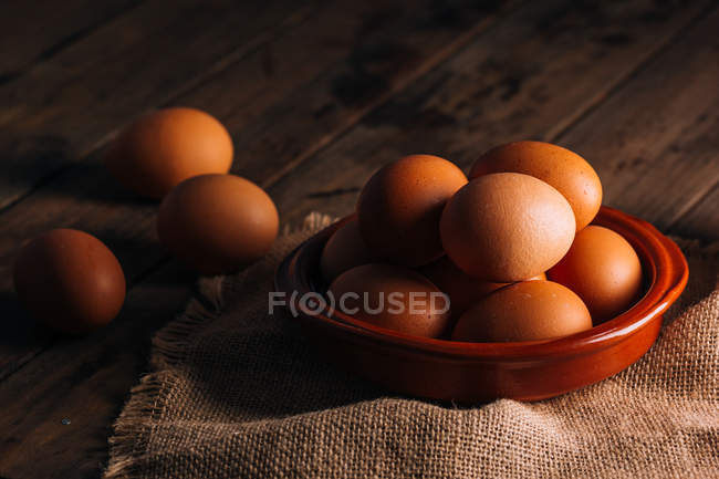 Chicken eggs with bowl and sackcloth on wooden table — Stock Photo