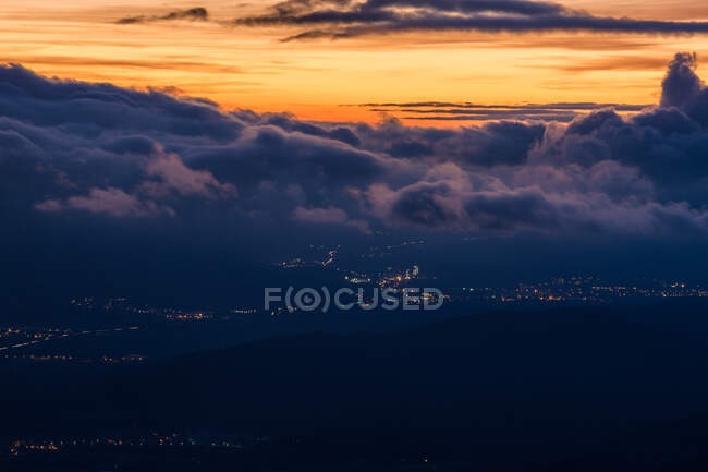 Landscape of hazy remote city lights in terrain under fluffy dark clouds with sunset sky — Stock Photo