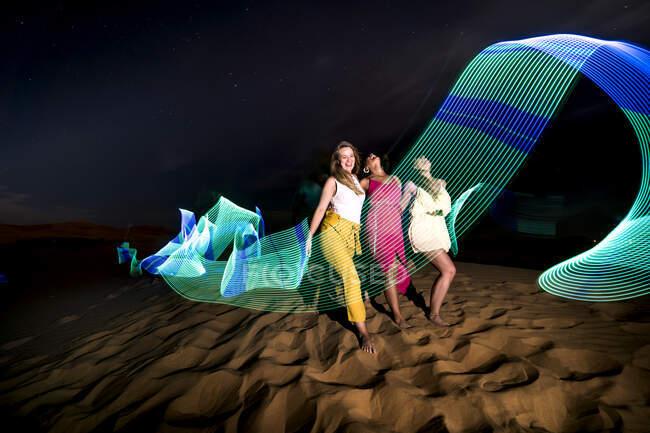 Pistas de luz de neón azul ondulando sobre mujeres alegres descalzas en el fondo del desierto oscuro por la noche en Marruecos - foto de stock